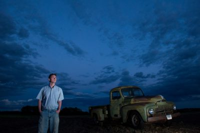 Photo: A young man looks at the sky near a 1951 International Harvester pickup truck at a farm near Bennet, Nebraska.