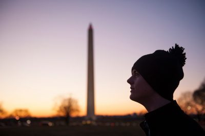 Photo: A teenage boy stands in front of the Washington Monument at sunset in Washington, DC.