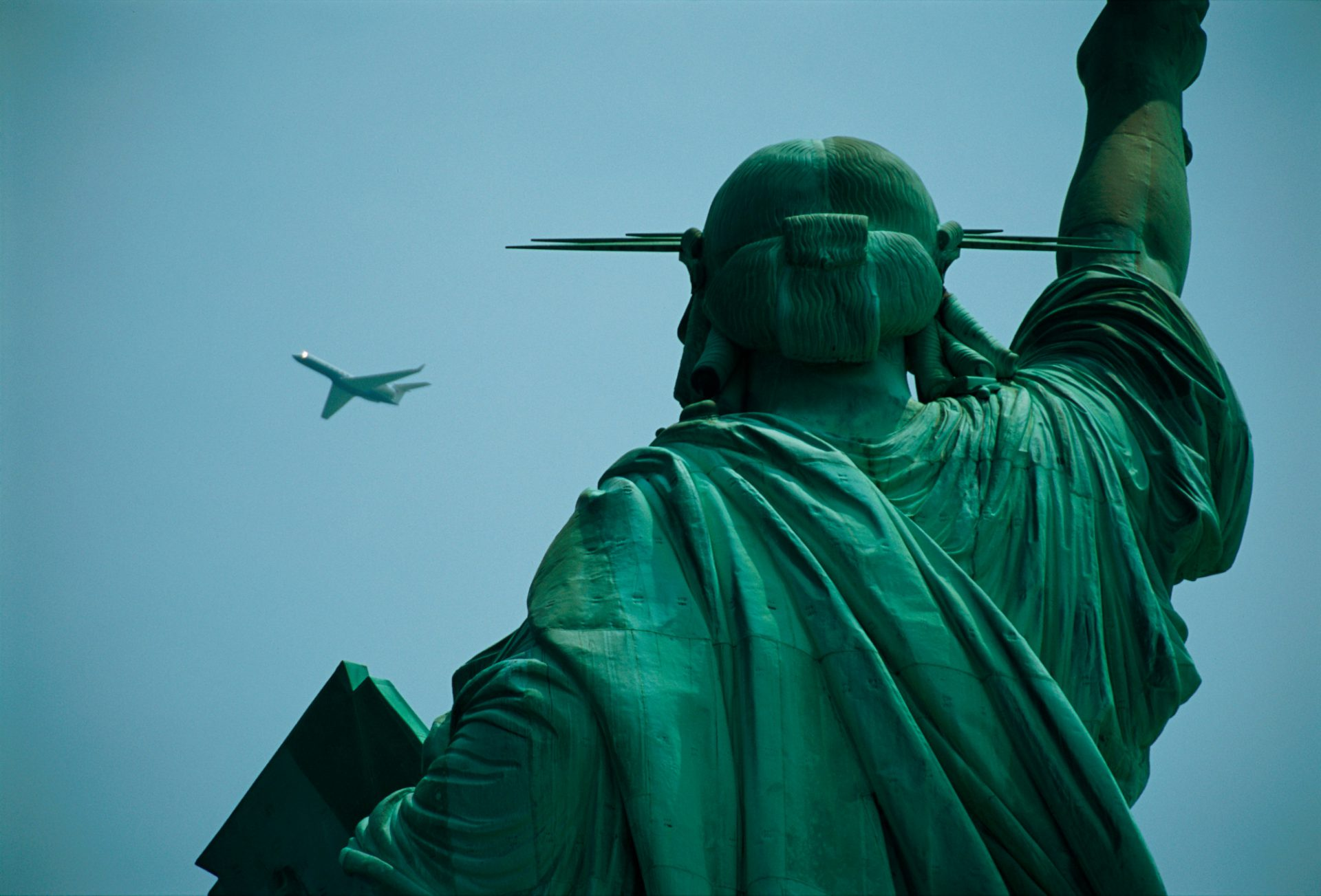 Photo: An airplane flies near the Statue of Liberty.