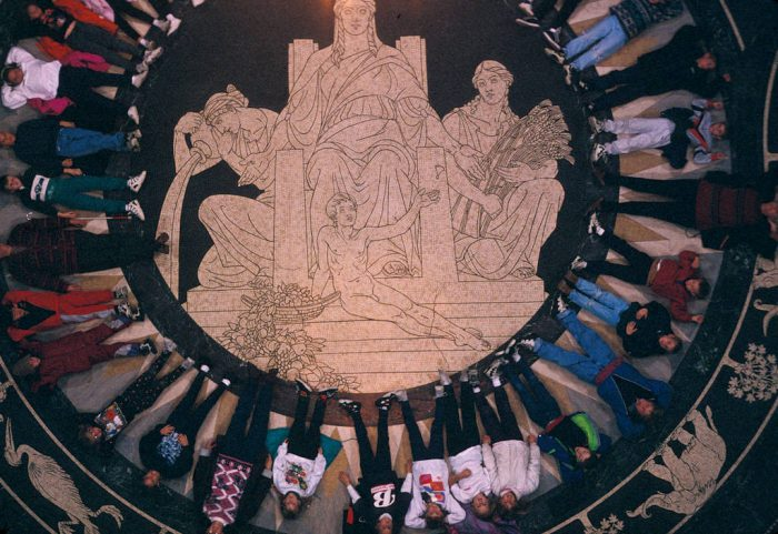 Photo: Students lie on the floor of the Nebraska State Capitol Building as they learn about its architectural features.