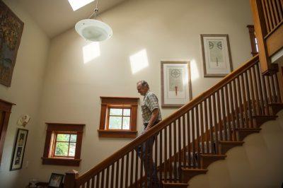 Photo: A man walks down his staircase.
