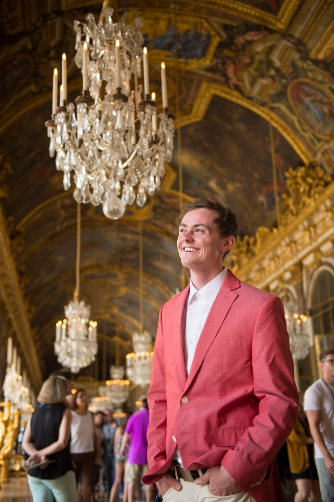Photo: A young man stands and smiles while touring the Palace of Versailles.