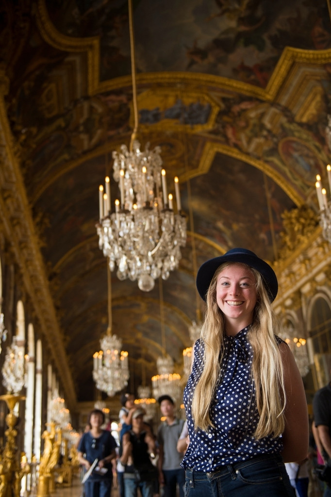 Photo: A young woman stands and smiles while touring the Palace of Versailles.