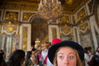 Photo: A young woman with eyes opened wide in the Palace of Versailles.