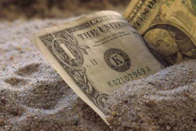 Photo: U.S. currency in the sand.