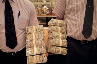 Photo: Two supervisors at the Federal Reserve in Boston each hold a stack of $100 bills, totaling in one million dollars and 22 pounds.