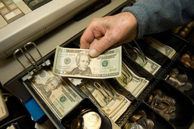Photo: Money shown being taken out of a cash register.