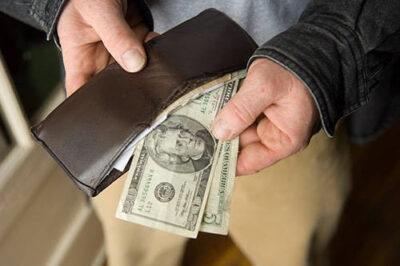 Photo: Money shown being taken out of a man's wallet.