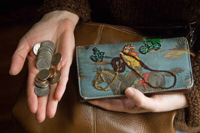 Photo: Coins being taken out of a woman's wallet.