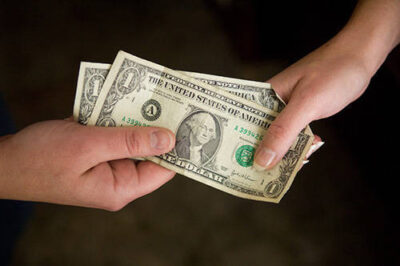 Photo: A close-up of two hands holding dollar bills.