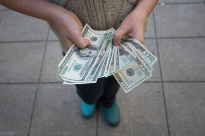 Photo: A 10-year-old girl fans out dollar bills.