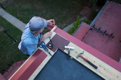 Photo: A man works on the roof of a historic home.