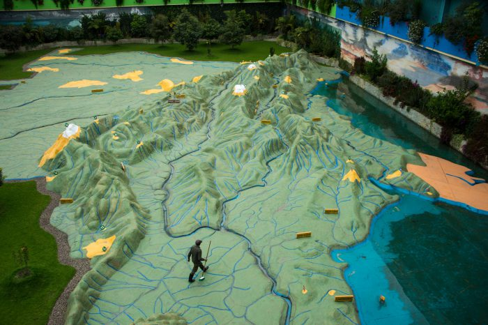 Photo: A staff member walks across a giant relief map of Columbia at Parque Jaime Duque, a tourist attraction near Bogota.