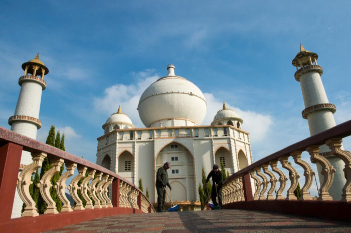 Photo: Staff members sweep the bridge leading to the replica of the Taj Mahal at Parque Jaime Duque in Columbia.