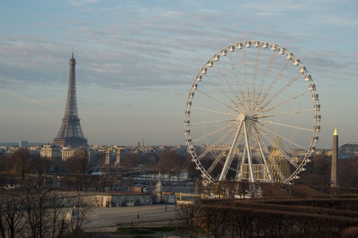 Photo: A Ferris wheel and the Eiffel Tower adorn the skyline in downtown Paris, France.