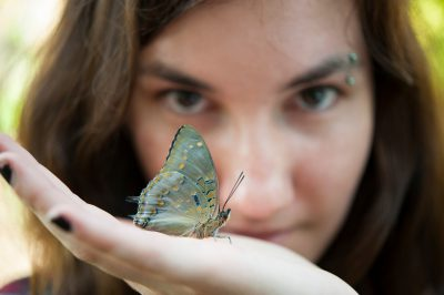 Photo: A young woman with blue-spotted charaxes butterfly (Charaxes cithaeron) in the butterfly garden at the Henry Doorly Zoo, Omaha, Nebraska.