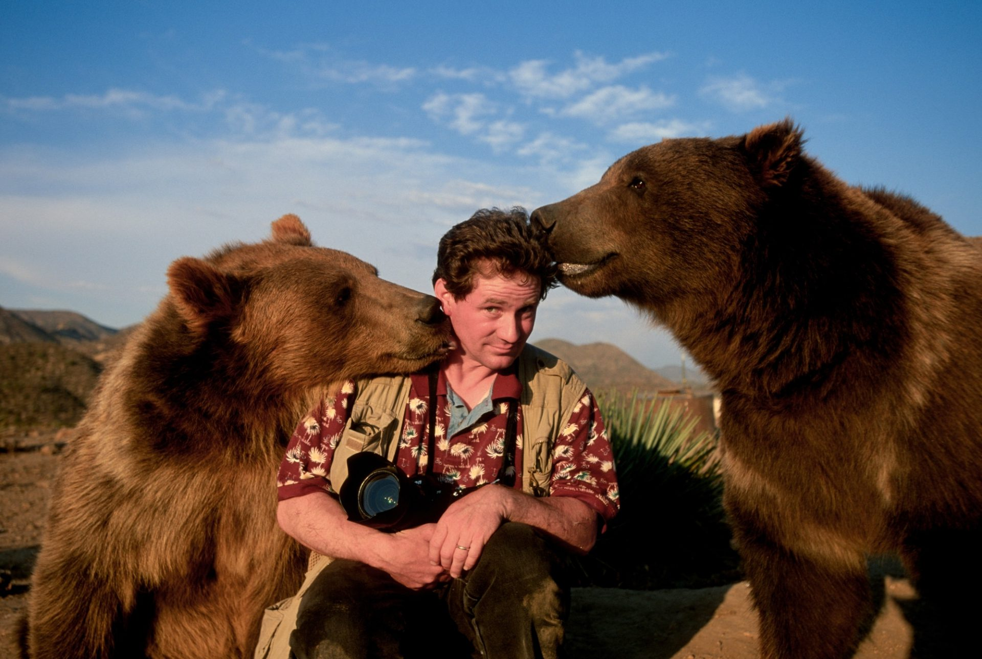 Photo: Joel Sartore gets a little affection from two trained grizzly bears.