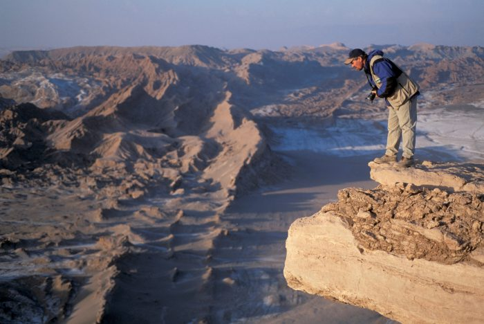 Photo: Joel Sartore peers over a cliff while on assignment in Chile's Atacama Desert.