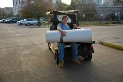 Photo: Cole Sartore holds onto the backdrop as he heads out of the Houston Zoo.