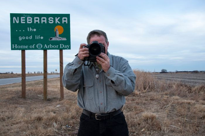 Photo: A photographer stops at the sign to Nebraska.