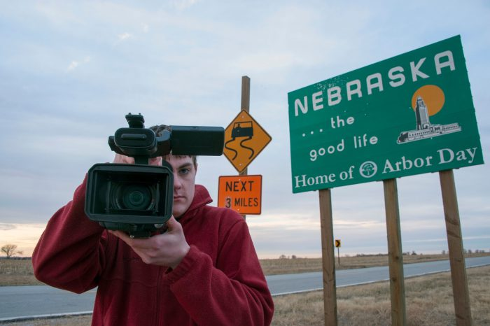 Photo: A videographer stops at the sign to Nebraska.
