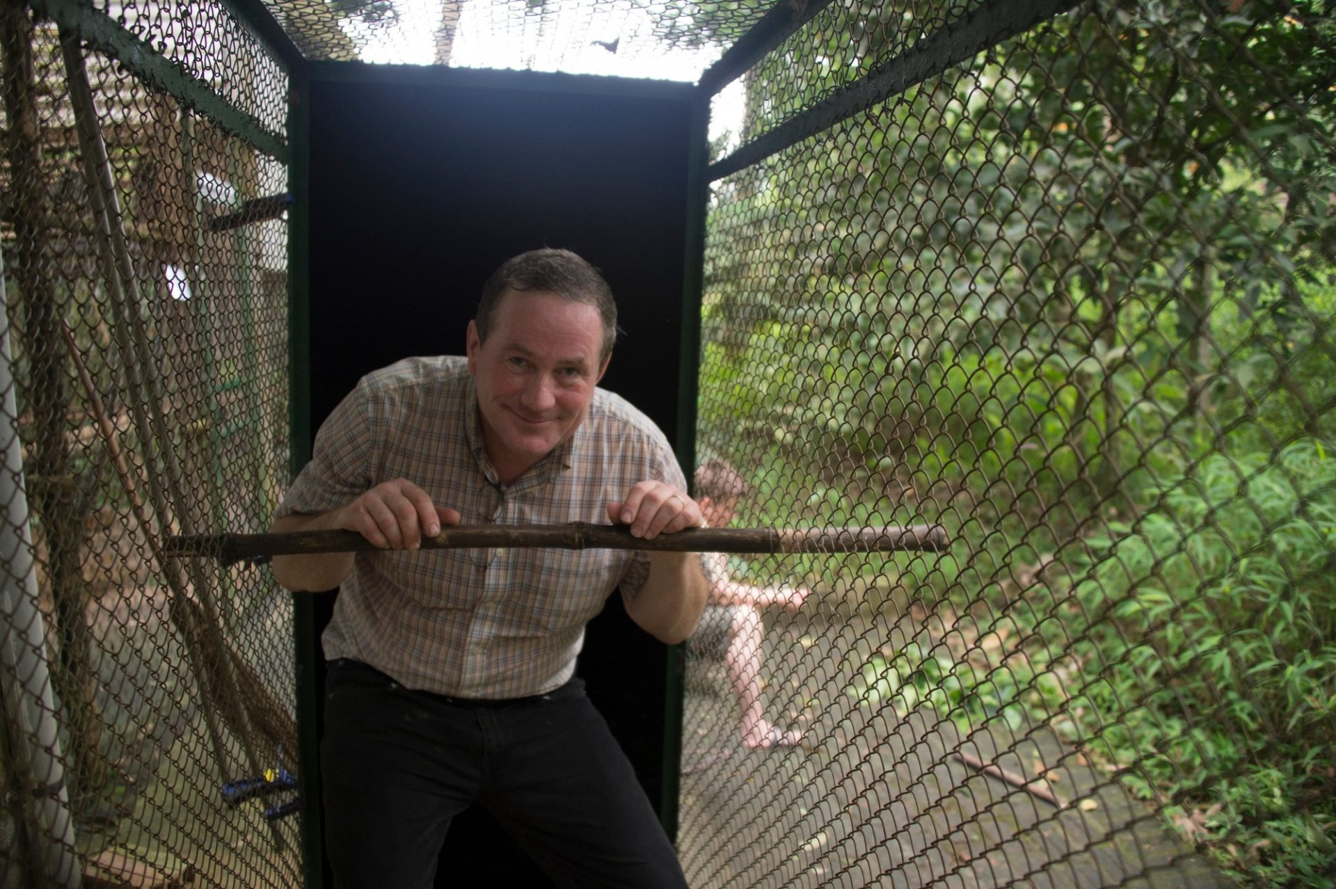 Photo: Joel Sartore poses inside a transfer cage at the Endangered Primate Rescue Center in Cuc Phuong National Park, Vietnam.