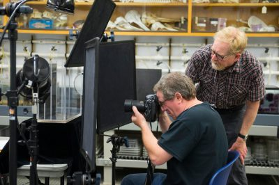 Photo: Joel Sartore and a staff member prepare for a photo shoot at the Monterey Bay Aquarium.