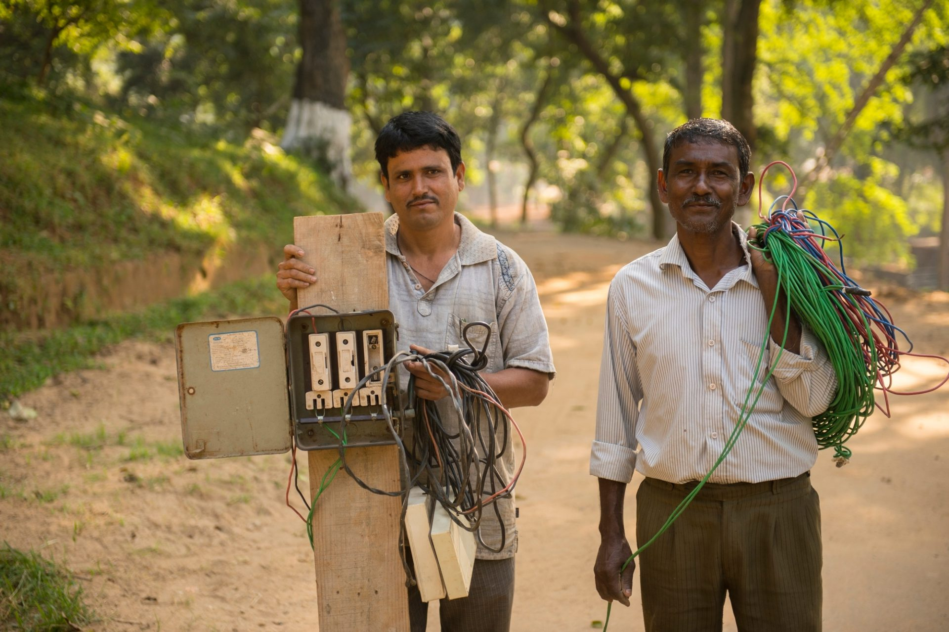 Photo: Two men improvise electricity for a Photo Ark shoot.