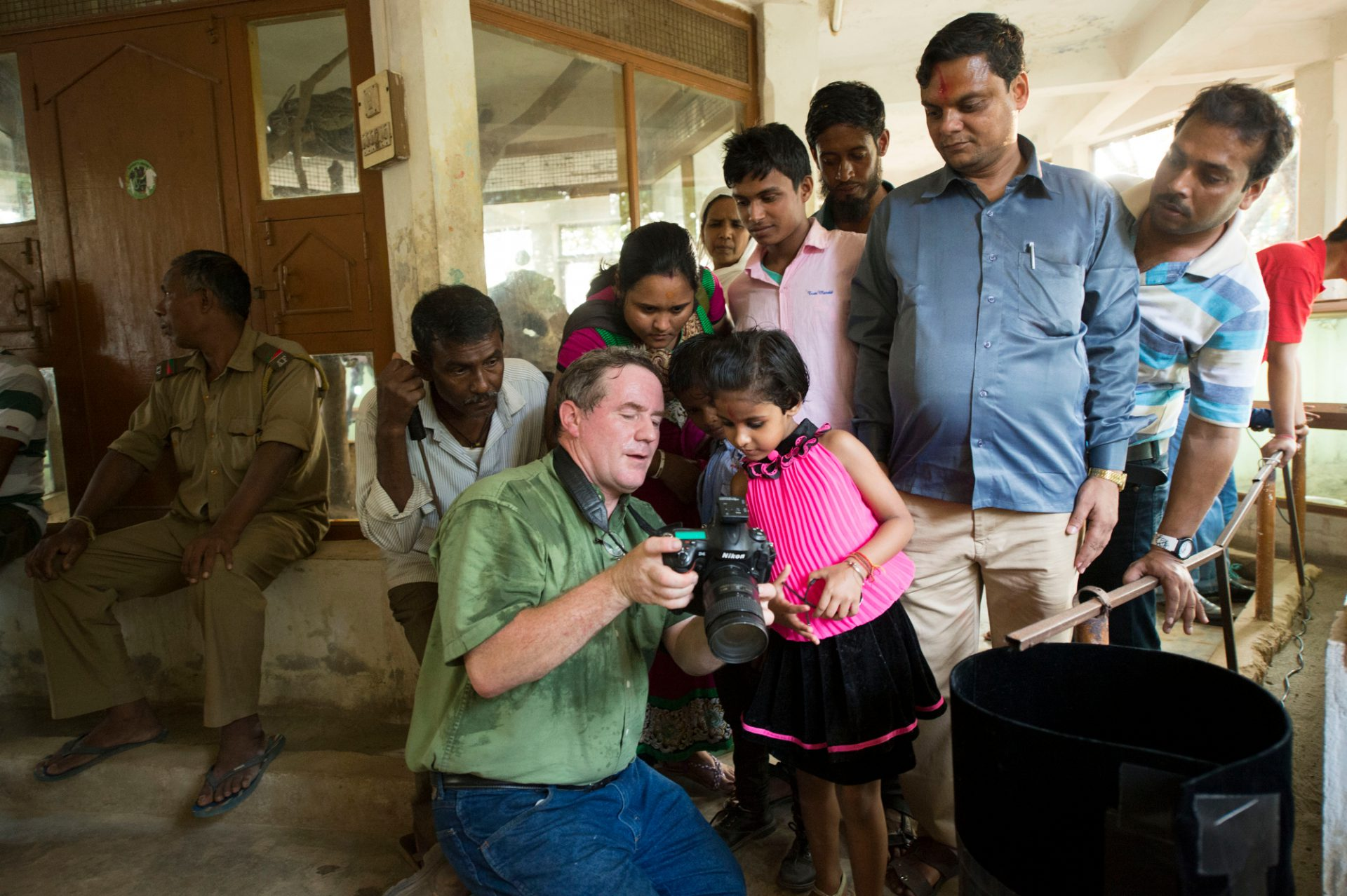 Photo: Joel shows an image to a group during a Photo Ark shoot inside the reptile house at the Assam State Zoo in Guwahati, Assam, India.