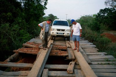 Photo: Joel Sartore and a local driver inspect a damaged bridge in Brazil's Pantanal region.
