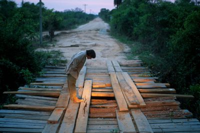 Photo: Joel's assistant, Daniel de Granville, inspects a damaged bridge in Brazil's Pantanal region.