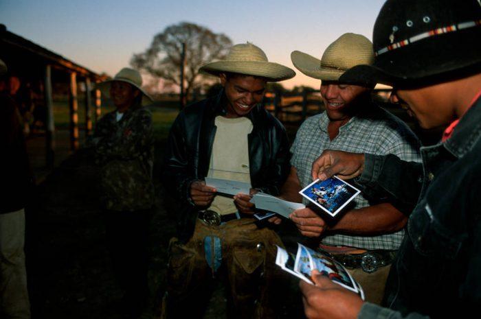 Photo: Cowboys, known locally as pantanieros, look through photos of themselves taken in the Brazilian Pantanal.