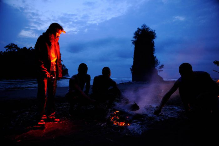 Photo: An expedition member stands by a camp fire on the coast of Bioko Island, Equatorial Guinea.