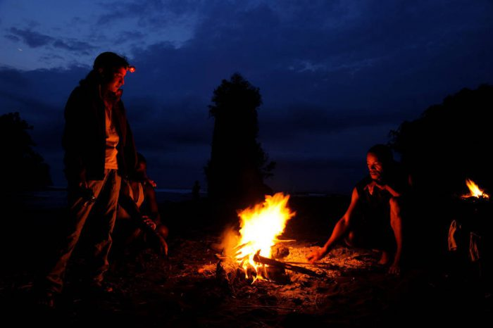 Photo: An expedition member stands by a campfire on Bioko Island, Equatorial Guinea.