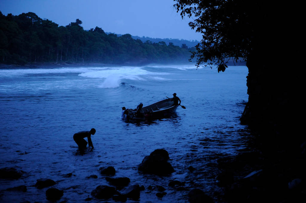 Photo: Expedition members paddle a boat off shore off the coast of Bioko Island, Equatorial Guinea.