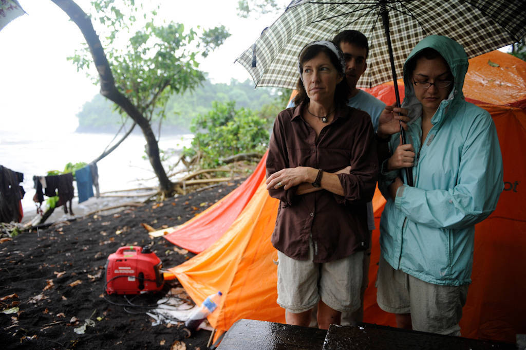 Photo: Expedition members talk amongst each other while standing in the rain on Bioko Island, Equatorial Guinea.