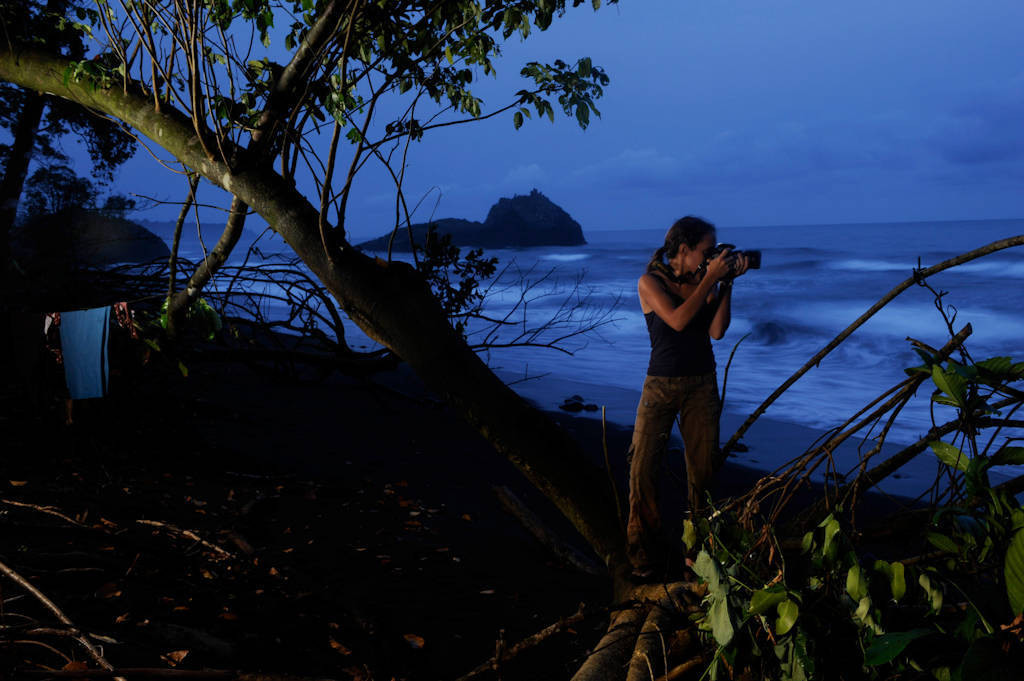 Photo: A biodiversity coordinator for BBPP (Bioko Biodiversity Protection Program) takes photographs on a beach in Bioko Island, Equatorial Guinea.