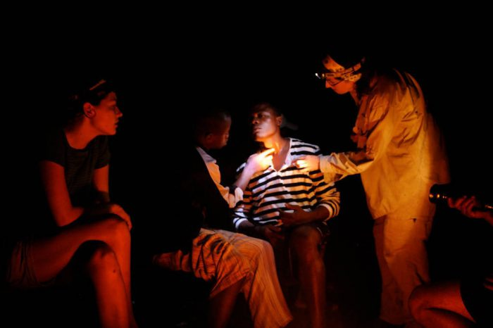 Photo: Expedition members around a camp fire attending to a young man's neck.