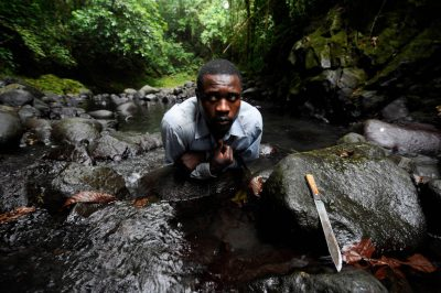 Photo: An expedition guide drinks from the Loari River near Camp Belmonte on Bioko Island, Equatorial Guinea.