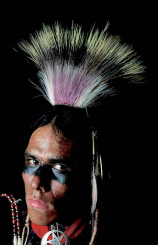 Photo: A member of the Ponca tribe (name available upon request) sits for a portrait in traditional regalia before a pow wow in White Eagle, OK.