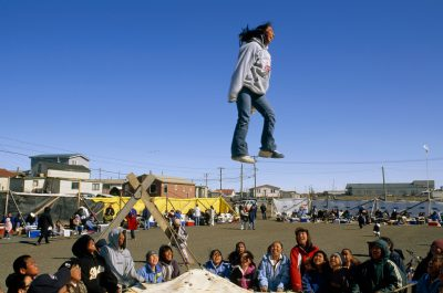 Photo: A young man is tossed high in the air during a traditional blanket toss, part of a whaling feast in Barrow.
