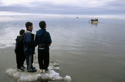 Photo: Young boys watch their elders compete in a seal skin boat race off the coast of Barrow.