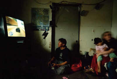 Photo: An unemployed native plays Grand Theft Auto from his condemned home in Point Lay. Unemployment runs extremely high in most villages.