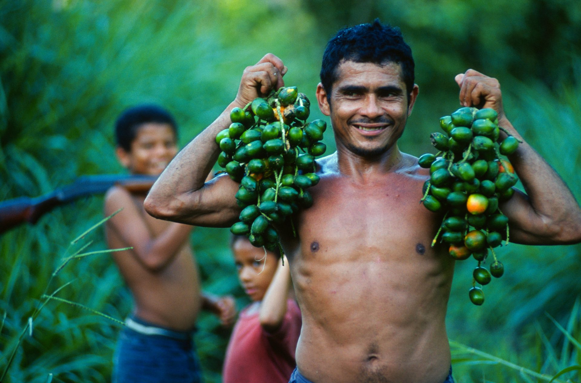 Photo: A Brazilian native shows off native fruits he gathered with his family at Quiandena, a village along the Capim River in the Brazilian Amazon.