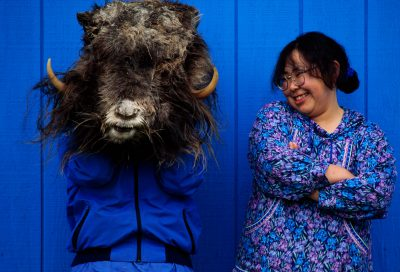 A local resident draws a laugh from her daughter by donning the head of a musk ox (Ovibos moschatus) recently shot by her husband. Sport hunters are allowed to kill approximately 70 of these animals, once extinct in Alaska, per year.