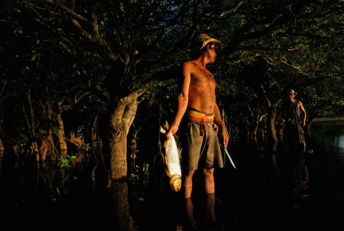 Photo: A ranch hand holds a dorado he has caught in the flooded forest on Barra Bansa ranch in Brazil.