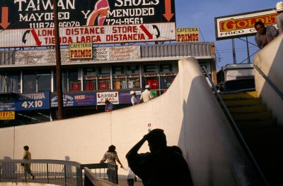 Photo: Pedestrians on a walkway are bombarded by loud signs written in English and Spanish in Laredo, Texas.
