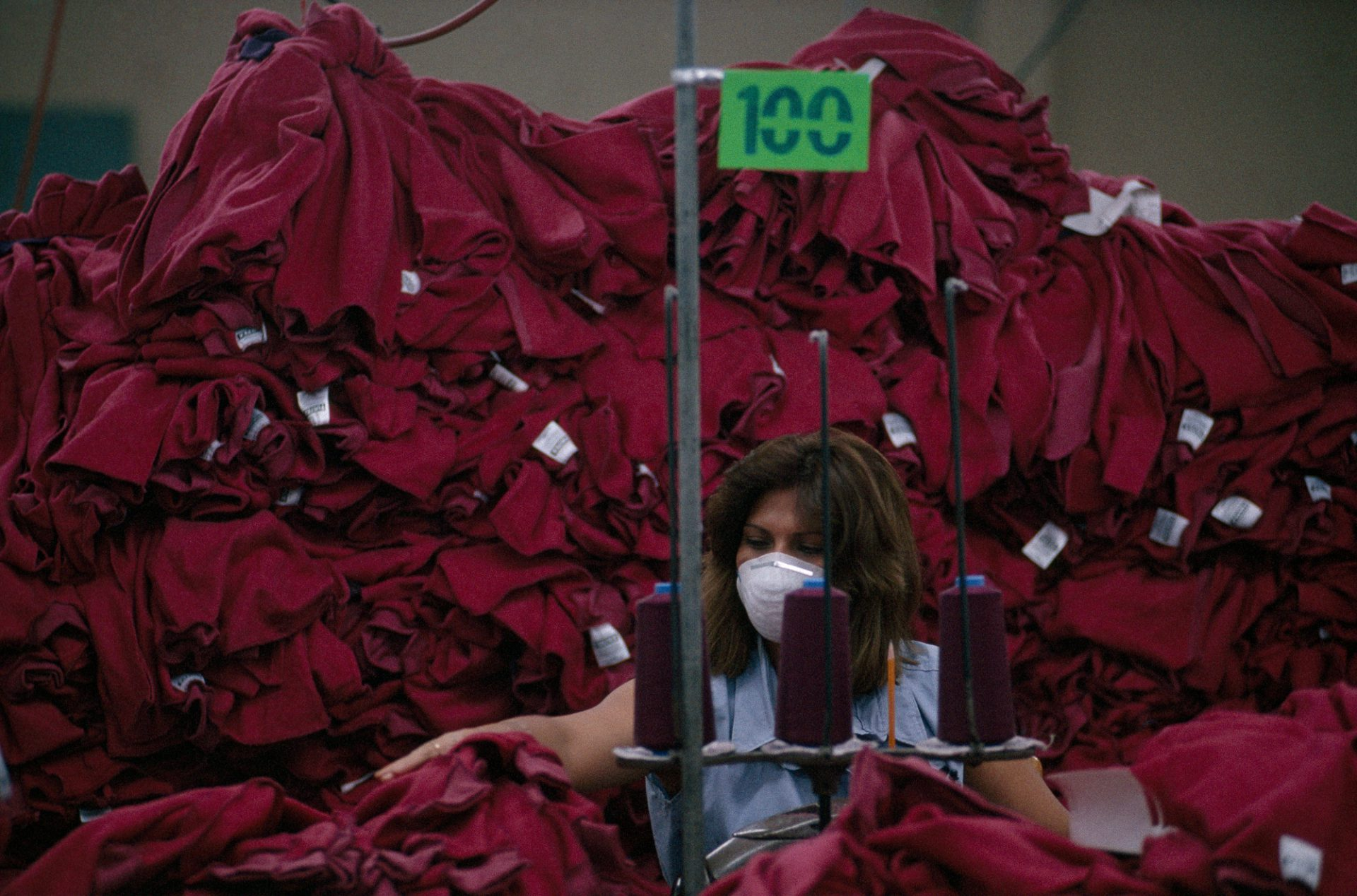 Photo: Surrounded by a mountain of maroon sweatshirts, top seamstress Rolanda Vasquez Hernandez assembles more sweatshirts to add to the pile.