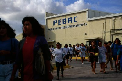 "Photo: At the end of a workday, employees of Pebac, a ""maquiladora,"" or assembly plant , leave to catch the buses that will take them home."