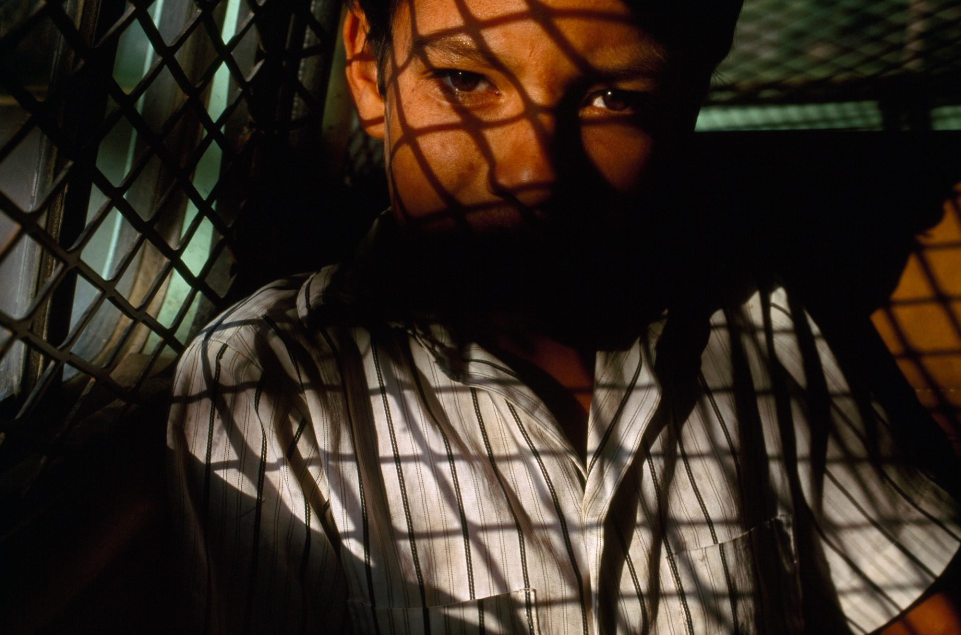 Photo: Criss-crossed by the shadows of containment bars in the back of a U.S. Border Patrol vehicle, a ten-year-old boy is driven back to his hometown of Matamoros after being caught sneaking into Brownsville, Texas.